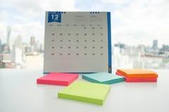 Post-it dans diverses couleurs sur le bureau pour le rappel de message avec le calendrier de décembre Photographie stock libre de droits