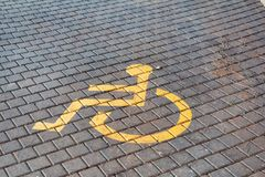 Post with disabled parking space and sign in front of parking bay in car park / Marked parking for people with special needs. Royalty Free Stock Photo