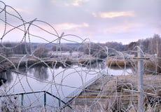 Post een omheining van prikkeldraad in de winter in vorst bij dageraad Royalty-vrije Stock Afbeelding