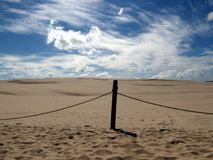 Post in sand dunes isolated on blue sky in National Park Poland. Post in endless sand dunes isolated on blue sky in the National Park Poland Royalty Free Stock Photos