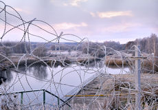 Post a fence of barbed wire in winter in frost at dawn Royalty Free Stock Image