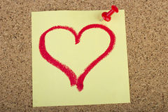 Post-it with heart shape drawn with lipstick. Post-it with a heart drawn with lipstick and put on a cork Royalty Free Stock Images