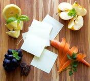 Post-Itanmerkungen mit Früchten, Gemüse, Kräuter auf hölzernem Schneidebrett Stockfotos