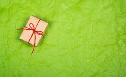Post- jordlott En ask med en gåva på en gräsplan skrynklade bakgrund kopiera avstånd Royaltyfri Foto
