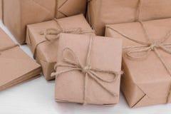 Post- jordlotter askar som slås in i hantverk, skyler över brister på en trätabell Post- eller leveransbegrepp royaltyfri bild