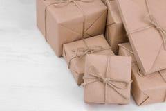 Post- jordlotter askar som slås in i hantverk, skyler över brister på en trätabell Post- eller leveransbegrepp royaltyfri fotografi