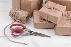 Post- jordlotter askar som slås in i hantverk, skyler över brister på en vit trätabell Post- eller leveransbegrepp royaltyfri fotografi