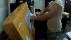 Post- kontorist Prepares frigöraren av den nyligen ankommna post- packen i kontoret stock video
