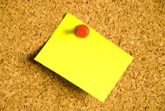 Post-it note. Colorful blank post-it note affixed to the corkboard Royalty Free Stock Images