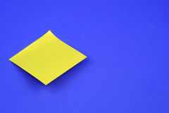 Post-it Note. Blank post-it on a blue background Royalty Free Stock Photos