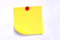 post-it note. A blank yellow post-it note attached with a red thumbtack or pushpin on a white background Royalty Free Stock Images