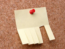 Post-it note. Blank yellow post-it note with cut slips affixed to corkboard with red pushpin Royalty Free Stock Image