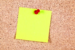 Post-it note. Yellow post it note attached to a board, with red push pin Stock Photo