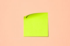 Post-it note. Blank green-yellow adhesive post-it note stuck on a pink wall stock photography