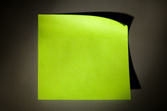 Post-it note. Blank green-yellow adhesive post-it note stuck on stainless steel surface of refrigerator  in cold illuminating cone Royalty Free Stock Photo
