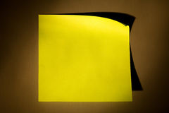 Post-it note. Blank yellow adhesive post-it note stuck on stainless steel surface of refrigerator in warm yellow illuminating cone Stock Photography