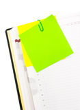 Post-it on the note book. With green clip Royalty Free Stock Photo