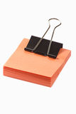 Post-it note with clip on white background. Orange post-it note with black clip isolated on white background Royalty Free Stock Photography