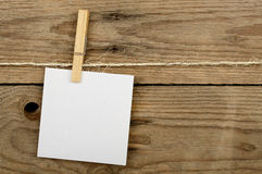 Post it note. With clothes peg against wooden surface Royalty Free Stock Photos