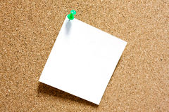 Post-it note with green pushpin on corkboard. Post-it note with green pushpin on corkboard Royalty Free Stock Photos