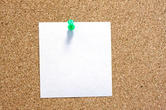 Post-it note with green pushpin on corkboard. Stock Photos