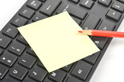 Post-it note, keyboard and pencil. Post-it note, keyboard and a red pencil stock photo