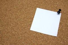 Post-it note with pushpin on corkboard. White post-it note with black pushpin on corkboard Royalty Free Stock Photo