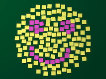 Post it note smiley face. A smiley face made up of square yellow and pink post it notes on a black background Royalty Free Stock Images
