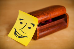 Post-it note with smiley face sticked on a box Stock Photo
