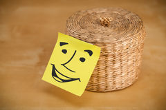 Post-it note with smiley face sticked on a box Royalty Free Stock Photography