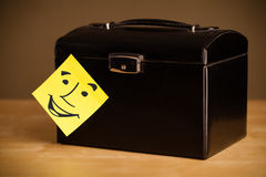 Post-it note with smiley face sticked on a box Royalty Free Stock Image