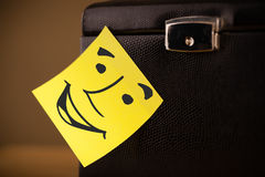 Post-it note with smiley face sticked on a box Stock Photography