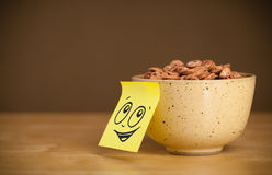 Post-it note with smiley face sticked on cereal bowl Stock Photos