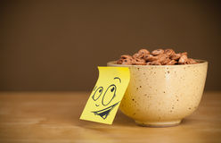 Post-it note with smiley face sticked on cereal bowl Royalty Free Stock Images