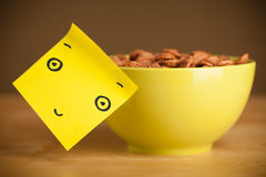 Post-it note with smiley face sticked on a cereal bowl Stock Photography