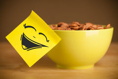 Post-it note with smiley face sticked on cereal bowl Stock Image