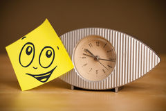 Post-it note with smiley face sticked on clock Stock Images