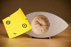 Post-it note with smiley face sticked on a clock Stock Photography