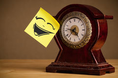Post-it note with smiley face sticked on clock Royalty Free Stock Image