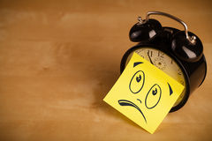 Post-it note with smiley face sticked on clock Royalty Free Stock Photo