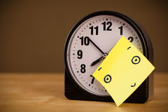 Post-it note with smiley face sticked on a clock Stock Photo