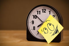 Post-it note with smiley face sticked on a clock Stock Images