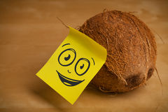 Post-it note with smiley face sticked on coconut Stock Photos