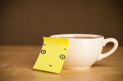 Post-it note with smiley face sticked on a cup Royalty Free Stock Images