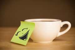 Post-it note with smiley face sticked on cup Stock Photography