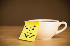 Post-it note with smiley face sticked on a cup Stock Photos