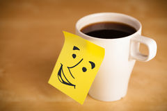 Post-it note with smiley face sticked on a cup Stock Photo