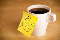 Post-it note with smiley face sticked on a cup Stock Images