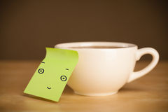 Post-it note with smiley face sticked on a cup Stock Image