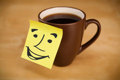 Post-it note with smiley face sticked on a cup Royalty Free Stock Photos